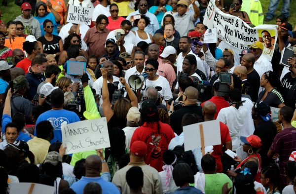 Rev. Traci Blackmon uses a megaphone to talk to a large group of demonstrators Thursday, Aug. 14, 2014, at the site where Mic