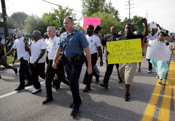 Thousands of demonstrators peacefully march down a street with members of the St. Louis County Police and Missouri Highway Pa