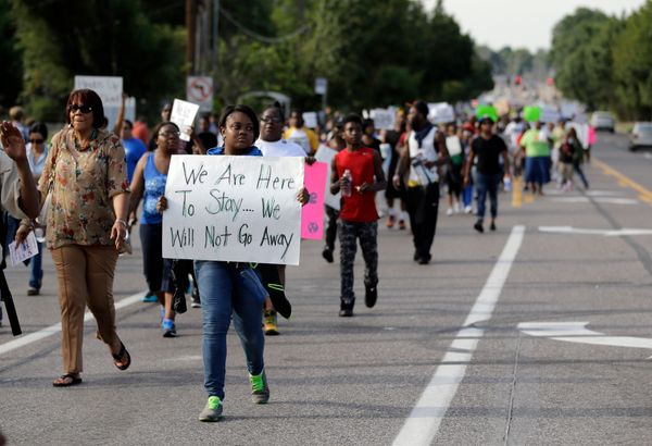 Demonstraters peacefully march down a street Thursday, Aug. 14, 2014, in Ferguson, Mo. The Missouri Highway Patrol seized con