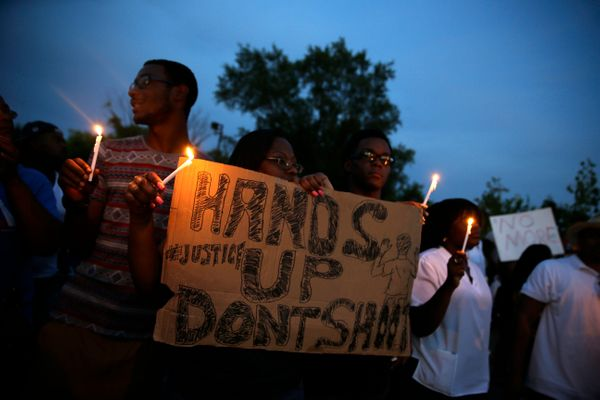 Demonstrators hold candles and signs Thursday, Aug. 14, 2014, in Ferguson, Mo. Hundreds of people protesting the death of  Mi