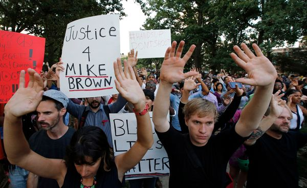 Supporters raise their hands during a rally at Meridian Hill Park, also known as Malcom X Park, Thursday, Aug. 14, 2014 in Wa