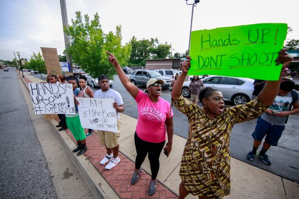 FERGUSON, MO - AUGUST 14:  Demonstrators shout slogans and hold up signs during a rally to protest the shooting death of an u