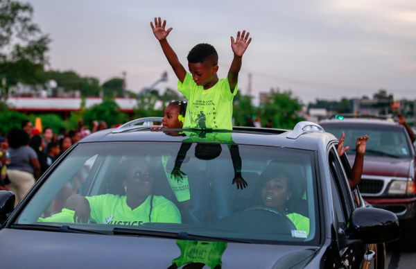 FERGUSON, MO - AUGUST 14:  Demonstrators raise their hands during a rally to protest the shooting death of an unarmed teen by