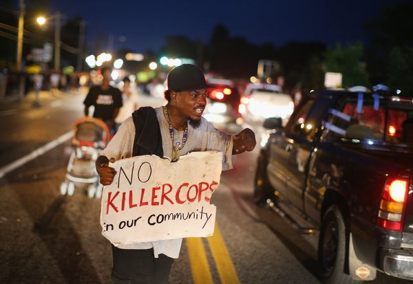 FERGUSON, MO - AUGUST 14:  A demonstrator holds a sign along West Florissant Avenue to protest the shooting death of Michael