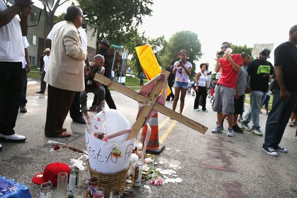 FERGUSON, MO - AUGUST 14:  Demonstrators protest at the spot where teenager Michael Brown was killed on August 14, 2014 in Fe
