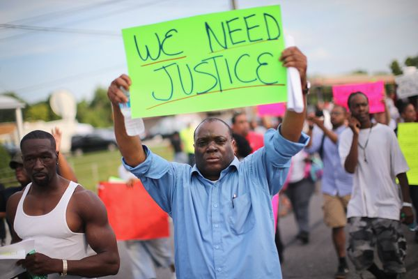 FERGUSON, MO - AUGUST 14:  Demonstrators protest the shooting death of teenager Michael Brown on August 14, 2014 in Ferguson,