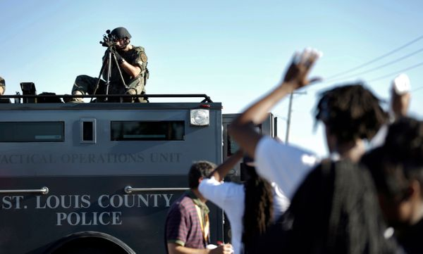 A member of the St. Louis County Police Department points his weapon in the direction of a group of protesters in Ferguson, M