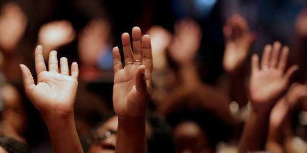 FILE - In this Aug. 17, 2014 file photo, people raise their hands during a rally at Greater Grace Church for Michael Brown, w