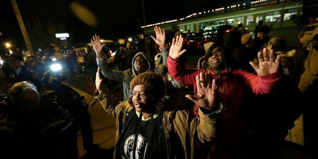 Barbara Jones joined by other protesters raise their hands up in the air as they protest Monday, Nov. 24, 2014, in Ferguson,