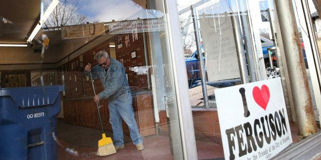 FERGUSON, MO - NOVEMBER 25:  A worker cleans up glass at a business that was damaged during a demonstration on November 25, 2
