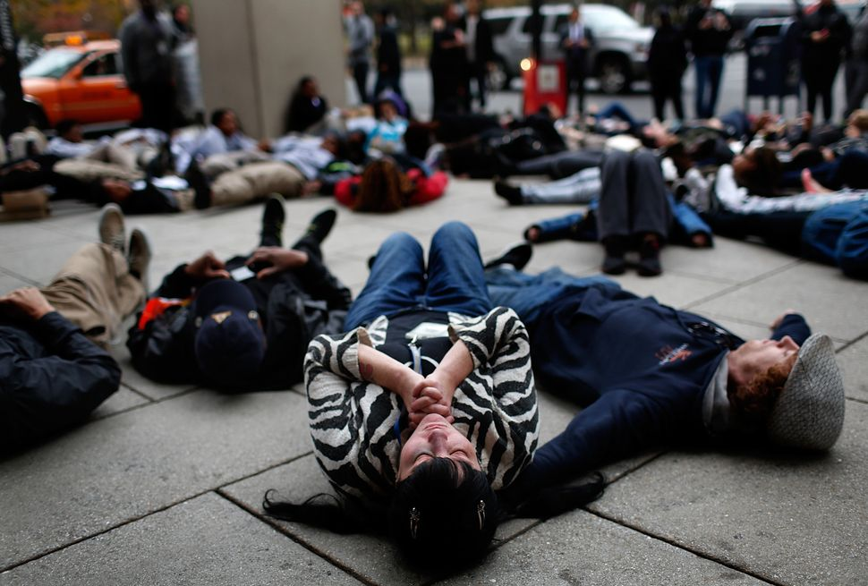 "Joy Cooney takes part in a ""die-in"" during a protest outside the Office of Police Complaints as part of a planned ""28 Hours f"