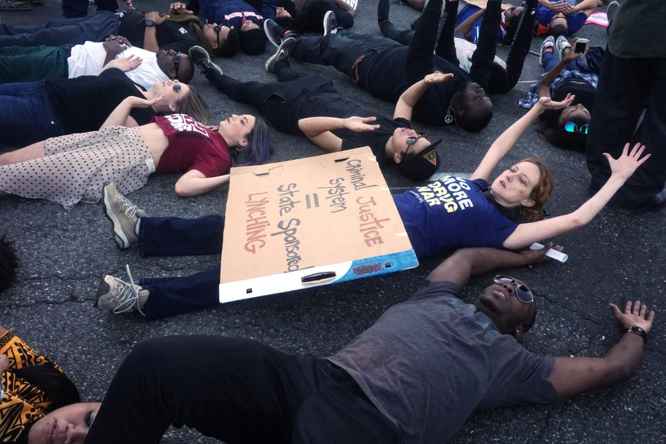 Protesters lie down at Martin Luther King Street  in reaction to the grand jury decision not to indict a white police officer