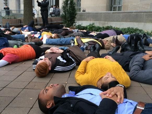 Protestors participate in a die-in for 4.5 minutes in front of the Department of Justice building in Washington, DC on Mon. D
