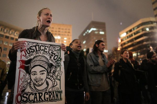 OAKLAND, CA - DECEMBER 3: Jessica Long of San Francisco holds a 'Justice for Oscar Grant' poster during a demonstration follo