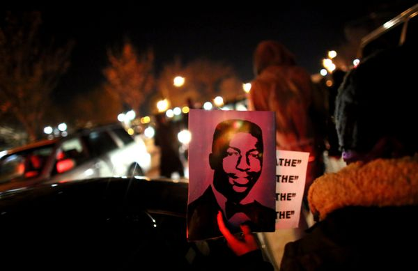 NEW YORK - DECEMBER 3: A protester holds up Garner's photo while walking on the West Side Highway December 3, 2014 in New Yor