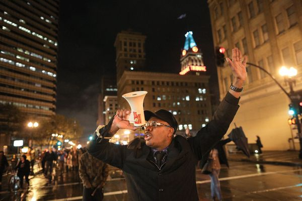 OAKLAND, CA - DECEMBER 3:  David Scott of Oakland leads a chant while marching down Broadway during a demonstration following