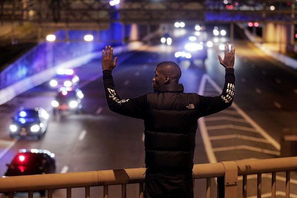 WASHINGTON, DC - DECEMBER 03:  Shaun Reid raises his hands as police follow demonstrators off Highway I-395 during a protest