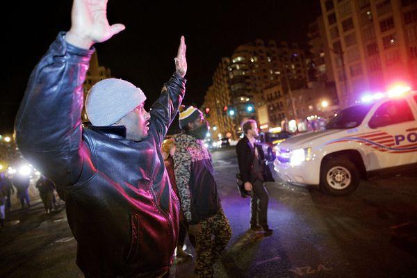 WASHINGTON, DC - DECEMBER 03: John Robinson, of Washington, DC, raises his hands while passing a police car as demonstrators