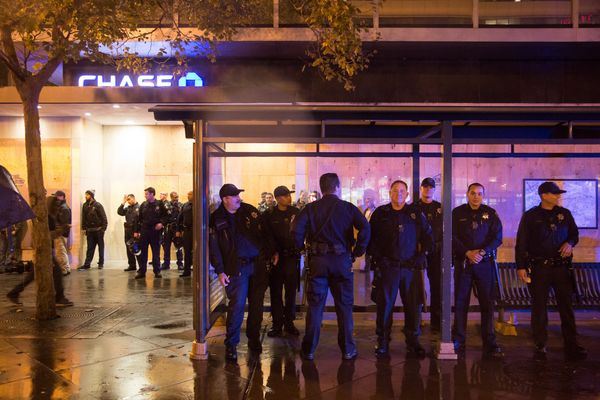 OAKLAND, CA - DECEMBER 3: Police officers take cover from the rain in a bus stop and under the awning of a Chase bank during
