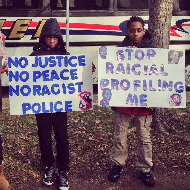 Young protesters hold signs in Freedom plaza on Saturday Dec. 13, 2014.