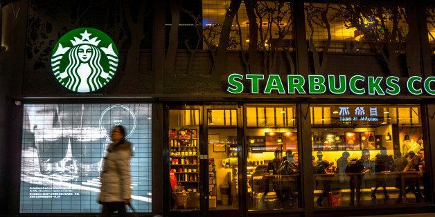BEIJING, CHINA - 2014/12/12: A girl pulls her luggage past a Starbucks coffee shop in Beijing South railway station.   There