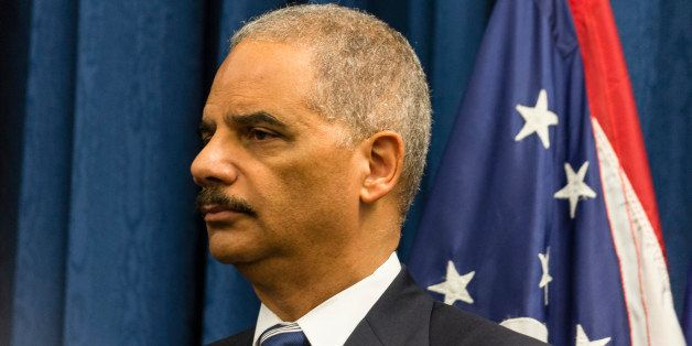 CLEVELAND, OH- DECEMBER 4: U.S. Attorney Eric Holder listens as U.S. Attorney Steve Dettlebach speaks to reporters at a press