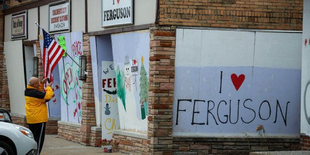 FERGUSON, MO - DECEMBER 02: Protestors draw graffiti on the walls of shops, were set fire during riots erupted after the Gran