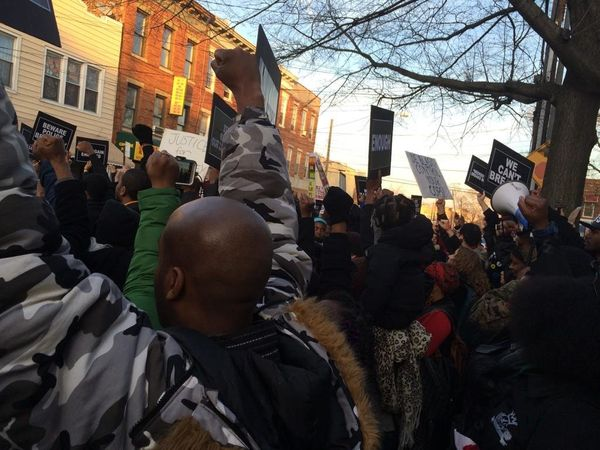 Demonstrators turn their backs to police during a protest march for Akai Gurley in Brooklyn on Dec. 27, 2014.