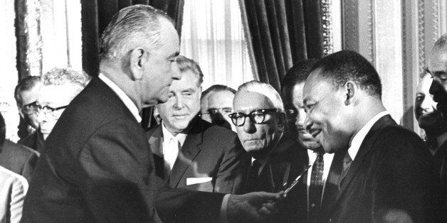 President Lyndon Johnson hands a souvenir pen to the Reverend Martin Luther King Jr after signing the Voting Rights Bill at t