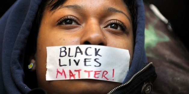 Penn State student Zaniya Joe wears a piece of tape over her mouth that says 'Black Lives Matter' during a Ferguson protest o