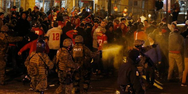 Police officers try to disperse the crowd of Ohio State fans trying to block High Street in Columbus, Ohio, as they celebrate