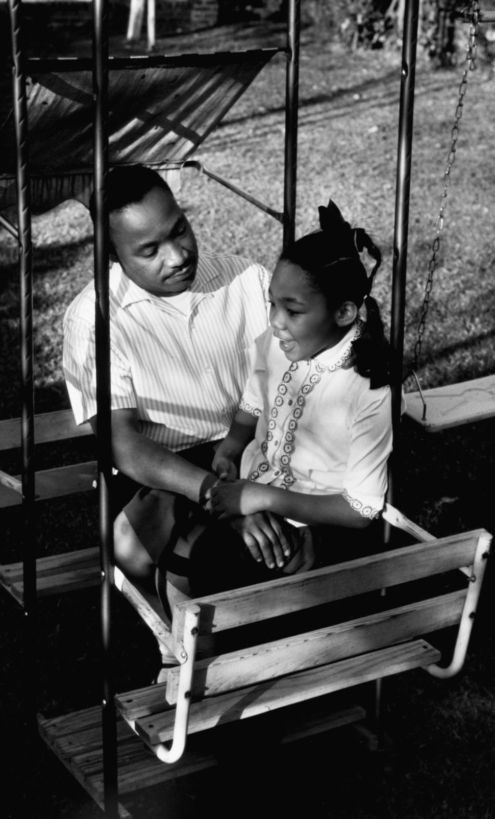 Martin Luther King Jr. talks with his daughter on a swing set in the backyard of their home in Atlanta.