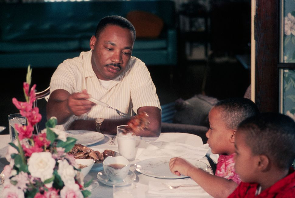 Martin Luther King Jr. serves pieces of chicken to his young sons Marty and Dexter at Sunday dinner on November 8, 1964.