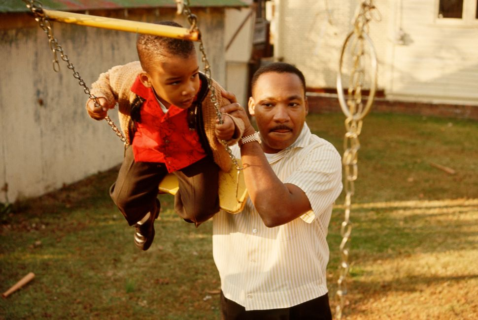 Martin Luther King Jr. pushes his young son Dexter on a swing set in their backyard, November 1960.