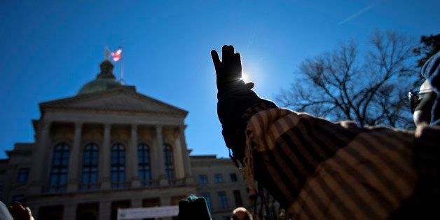 Malika Daniel, of Fairburn, Ga., raises her hand during a prayer song at the March For Life anti-abortion rally outside the S