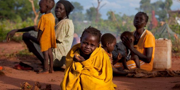 YIDA REFUGEE CAMP, SOUTH SUDAN - JULY 2: Asimara, 3, sits on the ground with her family without shelter after arriving at Yid