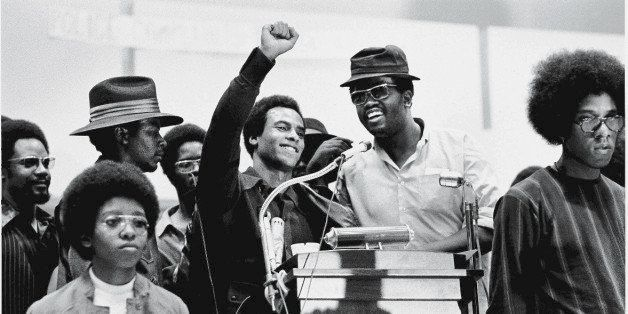 Black Panther Party co-founder Huey P. Newton (1942 - 1989) (center) smiles as he raises his fist from a podium at the Revolu
