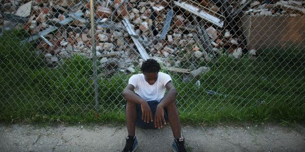 NEW ORLEANS - MAY 27:  A teenager sits in front of a demolished section of the B.W. Cooper housing projects May 27, 2008 in N