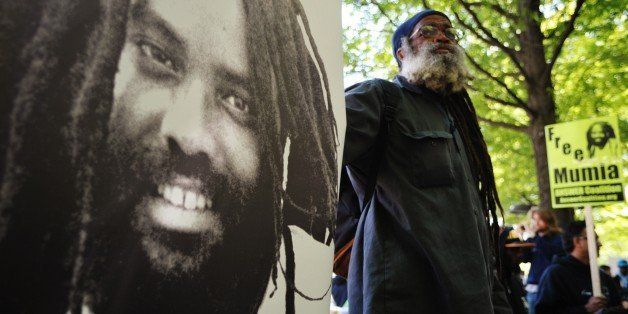 A protestor stands next to an image of Mumia Abu-Jamal  outside the US Department of Justice  on April 24, 2012 in Washington