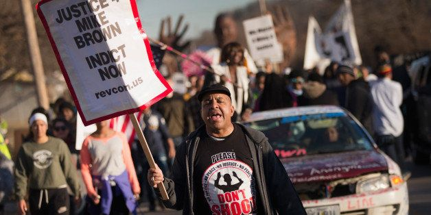 FERGUSON, MO - JANUARY 19:  Demonstrators remember Michael Brown with a Martin Luther King Jr. Day march from the apartment c