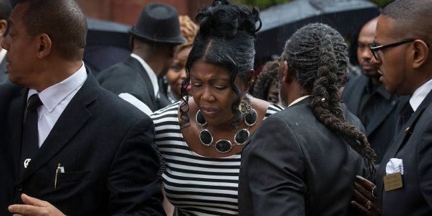 Sylvia Palmer, mother of Akai Gurley, leaves the funeral of her son at Brown Baptist Memorial Church, Saturday, Dec. 6, 2014,