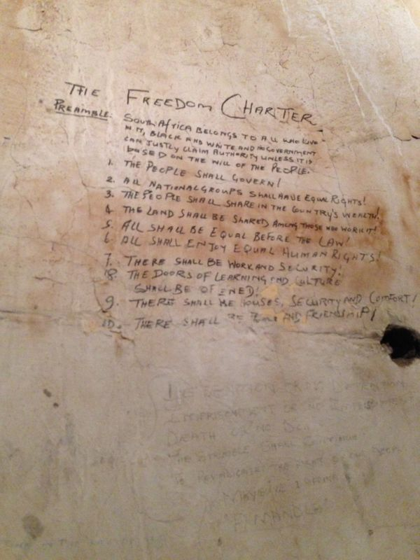 "An outline for ""The Freedom Charter,"" created by Mandela and his cell mates, is written on the walls of the cell."