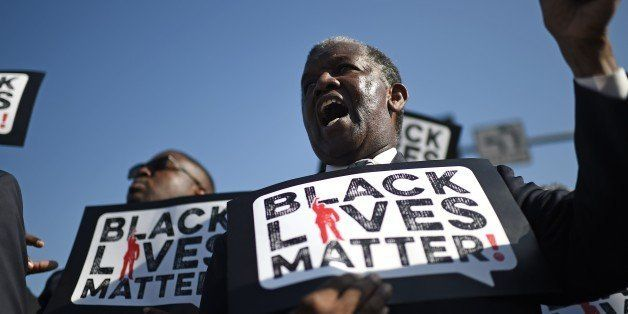 Men holding signs reading 'Black Lives Matter' march in the 30th annual Kingdom Day Parade in honor of Dr. Martin Luther King