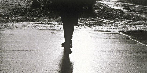Silhouette of person standing on wet sidewalk at night