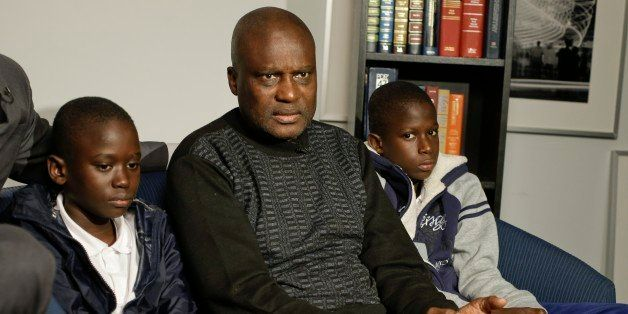 Amadou Drame, 11, and brother Pape Drame, 13, right, listen as their father, Ousmane Drame, responds to questions during a ne