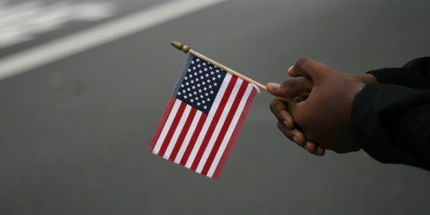 A small American flag held by African-American hands with a blurred background.