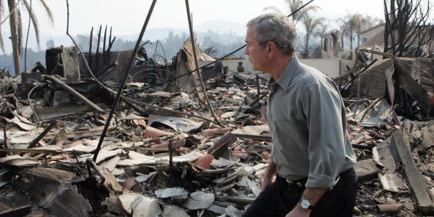 US President George W. Bush tours the remnants of a home after it was hit by a wildfire in San Diego, California, 25 October