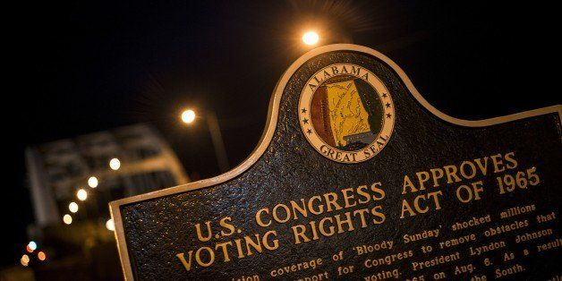 A plaque describes the 1965 Voting Rights Act at the base of the Edmund Pettus Bridge, where route 80 crosses the Alabama Riv
