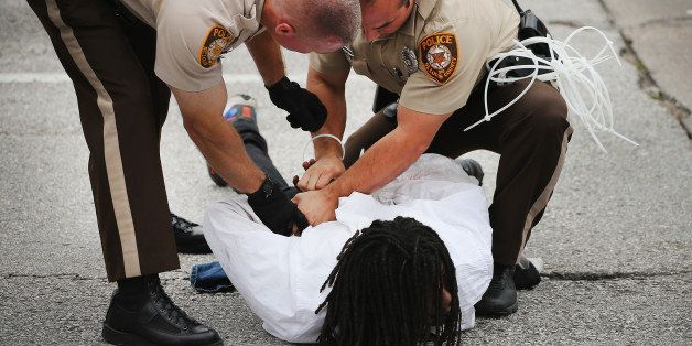 FERGUSON, MO - SEPTEMBER 10:  Police arrest a demonstrator during a protest along Interstate Highway 70 on September 10, 2014