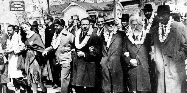 Dr. Martin Luther King Jr. links arms with other civil rights leaders as they begin the march to the state capitol in Montgom